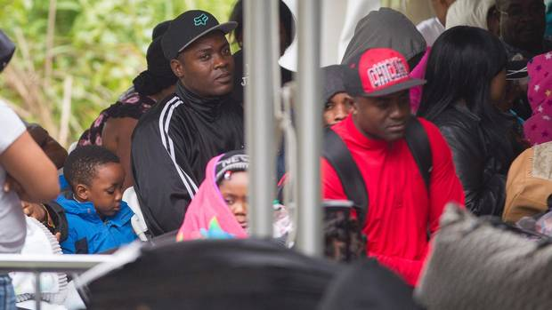 Refugees wait to be processed by the Royal Canadian Mounted Police after crossing the Canada/US border near Hemmingford, Quebec on August 6, 2017. (Geoff Robins/AFP/Getty Images)