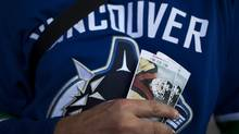 A Canucks fan holds a pair of tickets for game 7 of the Stanley Cup Final outside Rogers Arena in Vancouver, British Columbia, Wednesday, June 15, 2011. (Rafal Gerszak/The Globe and Mail)