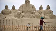 In this Sunday, June 17, 2012 photo, a woman shovels near sand sculptures of Confucius, centre, a famed thinker and philosopher in Chinese history, and his disciples, at a beach culture festival in Pingtan county, in southeastern China's Fujian province. (AP)