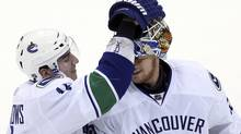 Vancouver Canucks goaltender Cory Schneider (R) is congratulated by teammate left wing Alexandre Burrows after their NHL hockey game against the Minnesota Wild in St. Paul, Minnesota, February 15, 2011. REUTERS/Eric Miller (ERIC MILLER)