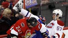Ottawa Senators' Chris Kelly (L) hits Montreal Canadiens' Benoit Pouliot during the first period of their NHL hockey game in Ottawa October 23, 2010. (BLAIR GABLE)