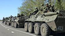 Russian servicemen drive armoured personnel carriers on the outskirts of the city of Belgorod near the Russian-Ukrainian border, April 25, 2014. (REUTERS)