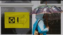 A woman carries an umbrella as she enters a polling station to vote in the federal election in Sidney, B.C., on Vancouver Island, on Monday May 2, 2011. (Darryl Dyck/The Canadian Press/Darryl Dyck/The Canadian Press)