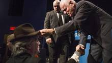 Barrck Gold's chairman and founder Peter Munk places his trademark hat on the head of new co-chairman John Thornton in Toronto on April 24, 2013 at the announcement of quarterly results. (Chris Young/THE CANADIAN PRESS)