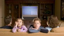 Family watching television, children facing away from television (Jupiterimages/Getty Images)