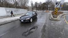 Drivers skirt around a pothole while turning onto Hoskin Avenue from Queen's Park Crescent on Jan. 13, 2014. (Fred Lum/The Globe and Mail)