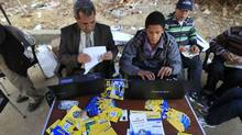 Muslim Brotherhood members help voters find their registration numbers before voting outside a polling station in the Manial neighbourhood of Cairo on Nov. 28, 2011. (Mahmud Hams/AFP/Getty Images/Mahmud Hams/AFP/Getty Images)