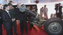 In this photo released on Tuesday, Aug. 21, 2012, by the official website of the Iranian Presidency Office, President Mahmoud Ahmadinejad, left, listens to an official, as he looks at a mortar launcher, while his Defense Minister Gen. Ahmad Vahidi, second left, looks on, during a ceremony to unveil Iranian-made weapons and marking the national day of Iran's defense industry. (Mohsen Rafinejad/AP)