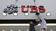 Workers repair a lighting fixture at a UBS bank branch in Zurich. (Alessandro Della Bella/AP)