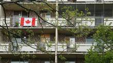 A Canadian flag flies from an apartment balcony in the Riverdale neighbourhood of Hamilton, Ontario on Tuesday, May 19, 2015. Riverdale is a highrise immigrant neighbourhood, third largest concentration of immigrants in Canada, and growing fast. (Peter Power For The Globe and Mail)