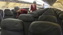 Air Canada Rouge flight attendants check through a plane at Toronto's Pearson Airport. (CHRIS YOUNG/THE CANADIAN PRESS)