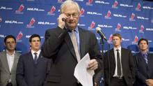 NHLPA Executive Director Donald Fehr (centre) glances at his notes as he stands in front of players, including Sidney Crosby (centre left) following collective bargaining talks in Toronto on Thursday October 18, 2012. (The Canadian Press)