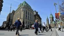 Pedestrians cross the street near Parliament Hill in Ottawa on April 27, 2011. (Sean Kilpatrick/THE CANADIAN PRESS)