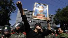 In this Sept. 15, 2012 file photo, a Chinese man holds up a portrait of former Chinese leader Mao Zedong during protests outside the Japanese Embassy in Beijing, China. (Ng Han Guan/AP)