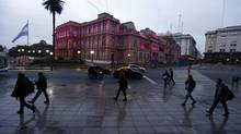 People walk in front of Casa Rosada Presidential Palace in Buenos Aires on Friday. (MARCOS BRINDICCI/Reuters)