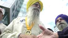 Fauja Singh, 93, being congratulatred after setting a record in his age class in the Toronto Waterfront marathon in this Sept. 28, 2003 file photo. (John Morstad/The Globe and Mail)