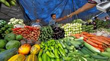 A customer pays after buying vegetables from a street side vendor in Mumbai.