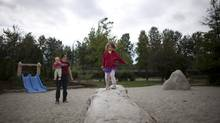 Kerith Stevens with her two children Linnea, 3, and Kaisa, 11 months, play at the 'natural' playground at Grandview Elementary school in East Vancouver, in 2011. (Rafal Gerszak for The Globe and Mail)