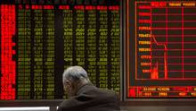 A investor rests near a display board showing the plunge in the Shanghai Composite Index at a brokerage in Beijing, Jan. 7, 2016. (Ng Han Guan/THE ASSOCIATED PRESS)