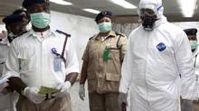 Nigerian health officials wait to screen passengers at the arrivals hall of Murtala Muhammed International Airport in Lagos, Nigeria, Monday, Aug. 4, 2014. Nigerian authorities on Monday confirmed a second case of Ebola in Africa's most populous country, an alarming setback as officials across the region battle to stop the spread of a disease that has killed more than 700 people. (Sunday Alamba/AP)