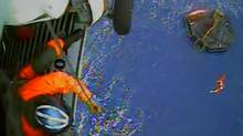 In this image made from video and released by the U.S. Coast Guard, a USCG rescue swimmer, in water at right, and a crew member use a hoist to bring up a survivors into a helicopter. (U.S. Coast Guard/AP)