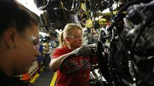 Employees install an engine on a Ford Motor Co. Super Duty Truck at the Ford Kentucky Truck Plant in Louisville, Kentucky, on Friday, Sept. 30, 2016. (Luke Sharrett/Bloomberg)