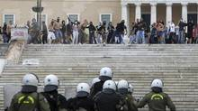 Protesters throw stones at riot police during clashes in front of the parliament in Athens on Tuesday Oct. 9, 2012. Why now do voters suddenly revile those who lent their governments the money? The answer to that question reveals the reason for the Greek riots and for the increasingly volatile unrest among the multitudes of unemployed youth in Spain, Portugal and Italy. It's summed up in one word, says Gwyn Morgan: Austerity. (Nikolas Giakoumidis/AP)