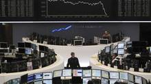 Traders are pictured at their desks in front of the DAX board at the Frankfurt stock exchange April 27, 2010. (MICHAEL LECKEL/REUTERS/Remote/Michael Leckel)