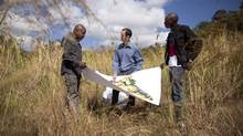 Mark Crandon, centre, of Russian company Renaissance Partners, and local employees Albert Mukomba, left, and Yannick Kitambo consult on a land development outside Lubumbashi. (John Lehmann/The Globe and Mail)
