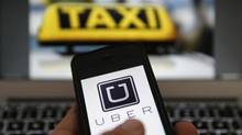 The logo of car-hailing service app Uber on a smartphone next to the picture of an official German taxi sign in Frankfurt. (Reuters/Kai Pfaffenbach)