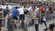 In this June 11, 2016 file photo, spectators run on the stands as clashes break out right after the Euro 2016 Group B soccer match between England and Russia, at the Velodrome stadium in Marseille, France. (Thanassis Stavrakis/AP)