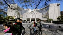 People walk past the headquarters of the People's Bank of China (PBOC), the central bank, as two paramilitary police officials patrol around it in Beijing, in this file photo. (Jason Lee/REUTERS)