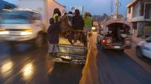 Vendors are transported in the early morning hours to bananas farms in the countryside, in Port-au-Prince, Haiti, Friday, Dec. 7, 2012. The vendors hope to bring back and sell the bananas at the local markets. Haitians suffered widespread hunger following an unusually active storm season this year and are likely to experience more, according to a study released Friday, Dec. 7, 2012. Nearly 70 per cent of the more than 1,000 households interviewed said they experienced moderate or severe hunger, the study found. (Dieu Nalio Chery/AP)