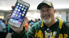 FILE - In this Sept. 19, 2014 file photo, John Mihalkovic, of Virginia Beach, Va., shows off his newly purchased iPhone 6 Plus outside the Apple store at Lynnhaven Mall in Virginia Beach.