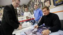 Former Toronto Argonaut and Washington Redskins quarterback Joe Theismann looks over a photo of himself brought in by a fan during an autograph signing in honour of the 100th anniversary of the Grey Cup. (Tim Fraser/Tim Fraser)