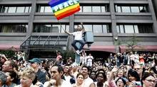 A man holds up a banner as thousands of people on Yonge Street watch the annual Pride Parade in Toronto on Sunday, June 28, 2009. (Nathan Denette/The Canadian Press)