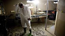 Eddy Marshall is overwhelmed by the damage to the basement in his High River home. (Jordan Verlage/THE CANADIAN PRESS)