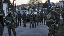 Russian forces stand at the entrance of a Ukrainian military base after storming the compound in the village of Belbek, Crimea, March 22. (MAURICIO LIMA/NYT)