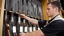 "Patrick Deegan displays long guns at a gun store in Calgary Sept. 15, 2010. A man who a judge says has an ""obsession with warfare and weaponry"" has been sent to jail for threatening to kill people with a machine gun at the Calgary Stampede last summer. Deegan, 29, was sentenced Thursday to two years less a day. (Jeff McIntosh/THE CANADIAN PRESS)"