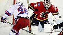 New York Rangers' Danny Kristo, left, looks on as Calgary Flames goalie Karri Ramo, from Finland, blocks his shot during second period NHL preseason hockey action in Calgary, Monday, Sept. 23, 2013. (Jeff McIntosh/THE CANADIAN PRESS)