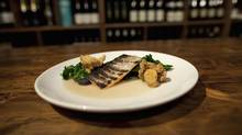 The fresh trout is served with punchy braised kale and a pair of perfect fried clams. <137>Trout at Skin and Bones, 980 Queen St East in Toronto Feb 6, 2013. (Moe Doiron/The Globe and Mail)<137><137><252><137> (Moe Doiron/The Globe and Mail)