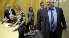Toronto Mayor Rob Ford, right, smiles as he walks past (L-R) City Manager Joesph Pennachetti, Deputy Mayor Doug Holyday, and TTC Chair Karen Stintz, following a news conference announcing that the city will pursue a subway extension into Scarborugh, subject to provincial and federal funding, in Etobicoke, July 12 2013. (J.P. MOCZULSKI For The Globe and Mail)
