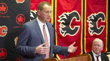 Calgary Flames' new general manager Brad Treliving, left, speaks after being introduced by the team's president of hockey operations, Brian Burke, in Calgary on Monday, April 28, 2014. (Larry MacDougal/The Canadian Press)