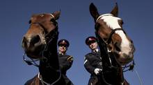 Honest Ed, ridden by Staff Inspector William Wardle, left, and Tecumseh, ridden by Sergeant Jim Patterson, are shown training in Toronto this week. (Moe Doiron/The Globe and Mail)