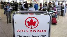 Air Canada travellers wait at the check-in area in Montreal in this file photo. (OLIVIER JEAN/REUTERS)