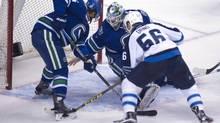 Vancouver Canucks defenceman Luca Sbisa (5) tries to stop Winnipeg Jets Marko Dano from getting a shot past Vancouver Canucks goalie Jacob Markstrom (25) during second period NHL action in Vancouver on Monday, March 14, 2016. (JONATHAN HAYWARD/THE CANADIAN PRESS)