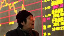 An investor looks at the stock prices monitor at a private securities company in Shanghai. (Str/AP)