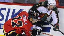 Minnesota Wild's Matt Cullen (R) is pushed against the boards by Calgary Flames' Jarome Iginla during the second period of their NHL hockey game in Calgary, Alberta, December 20, 2011. REUTERS/Todd Korol (Todd Korol/Reuters)