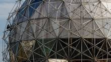 A worker hangs on the side of the geodesic dome roof of the Science World building while performing maintenance in Vancouver, B.C., on Wednesday September 26, 2012. The latest commercial for Science World British Columbia was barred from TV for being too violent. In the ad, produced by agency Rethink, an irrepressibly cheerful man is kicked in the groin, shot by an arrow, set on fire, and hit by a bus to illustrate how optimists feel less pain. (DARRYL DYCK/THE CANADIAN PRESS)