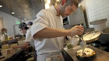 Sous chef Nick Adams puts on the finishing touches of a dish of Poutine at the Salt House Friday in San Francisco, California. (David Paul Morris/Globe and Mail)